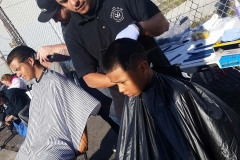 Santos is getting his hair cut on the streets in downtown San Diego.