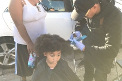 Wylie from the Country Club Barber shop cuts little homeless girl Lauren hair.