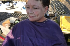 A homeless woman smiles after looking at her new haircut