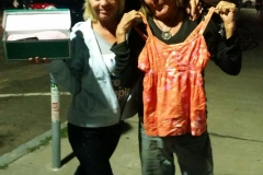 San Diego homeless ladies Terry and her friend hold up new shoes and tank top.