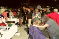 Tammy and Parker praying for a San Diego homeless women after she cut her hair at our homeless Thanksgiving event.