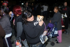 A homeless women in San Diego holds up her dog on the streets of San Diego.