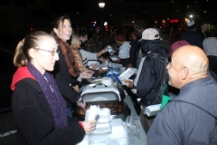 Anne is all smiles as she serves food to the homeless this Monday night.