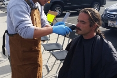 Streets of Hope San Diego volunteer trimming a homeless man's goatee