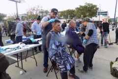 Two San Diego homeless men have their hair cut.