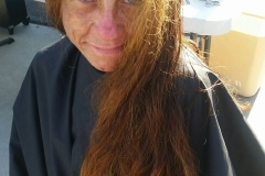 BEFORE: A homeless woman smiles as she gets ready for her hair cut!