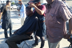 A homeless black man gets his hair cut downtown.