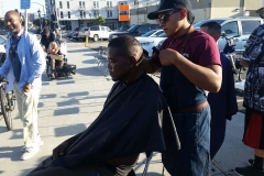 A homeless black man gets his hair trimmed.