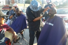 Roberto trims a homeless man's goatee in downtown San Diego.