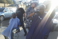 Sprays of light shine down on Mario as he cuts a homeless man's hair.