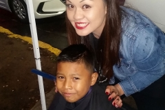 Tammy cuts Santos' hair at our San Diego downtown homeless event.