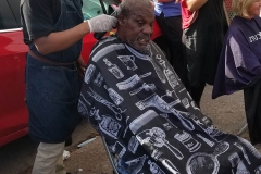 A homeless man get his hair cut by Wylie from Country Club Barber Shop