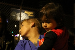Streets of Hope San Diego volunteer holds a little homeless girl at our Thanksgiving event