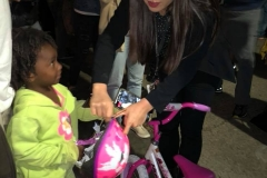 Tammy presents 3 year old homeless girl Christiana a new bike and helmet for Christmas.