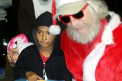 Streets of Hope San Diego Santa gifts a race car to a homeless boy at our Christmas event.