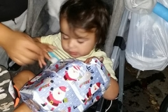 A homeless toddler opens her Christmas gift at the Streets of Hope San Diego homeless Christmas event.