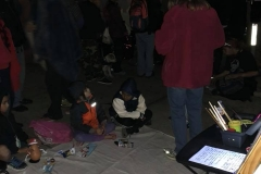 Homeless kids sit on the street in front of the mural being painted at our Christmas event.