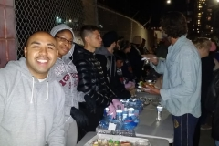 Homeless volunteers feed the homeless on Christmas as the line up in the food line.