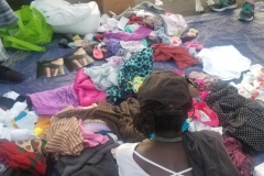 A homeless women sifts through some of the donated clothes remaining.