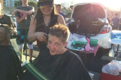 Sun lines paint the smile of a homeless women getting her hair cut on Easter