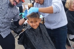 A homeless boy's hair gets cut and he's excited at our San Diego Easter event.