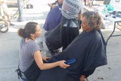 Asking a homeless lady how she wants her hair styled and cut.