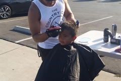 The start of a homeless boy's haircut .